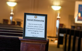 Sign post saying 'Social Distancing' at a funeral hall